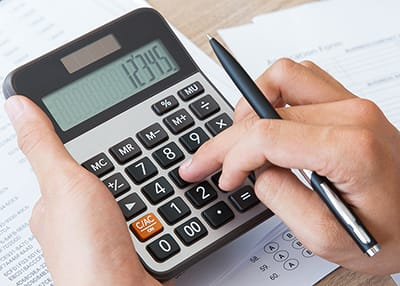 person typing numbers into a calculator