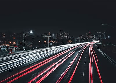 cars driving down highway at night